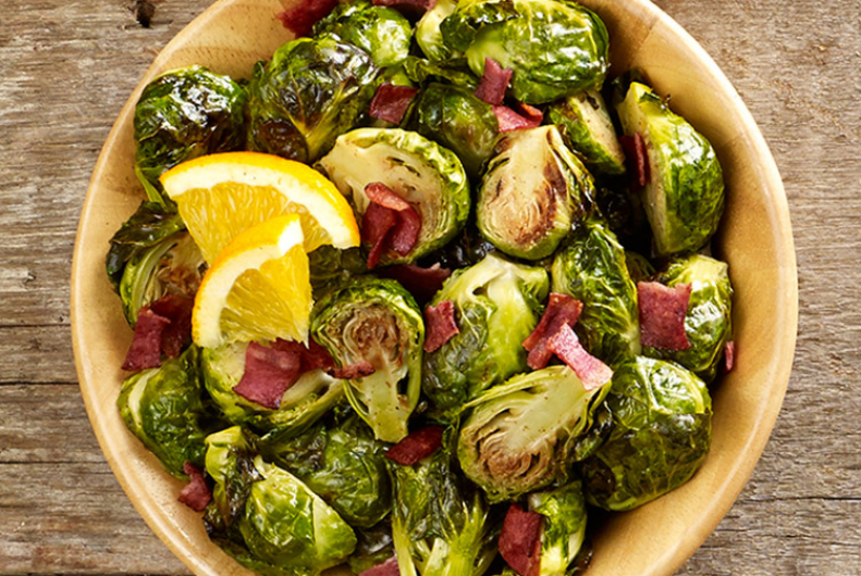 - Ingredients:  6 slices turkey bacon  20 brussels sprouts  juice of one naval orange (I got about ¼ cup) 1 shallot, peeled and quartered ¼ cup olive oil 2 teaspoons stone ground mustard 2 teaspoons cane vinegar (any kind would work) 2 teaspoons real maple syrup ½ teaspoon of saltDirections:1. Remove the base of the brussels sprouts by cutting off just the very bottom part of the stem (it's white). If you cut too much off, the leaves will fall apart, so be careful. Slice the brussels sprouts in half.2. Puree the orange juice, shallot, olive oil, mustard, vinegar, maple syrup, and salt in a food processor until a smooth sauce forms. Set aside.3. Cook the turkey bacon in a hot pan. Drain on paper towels. When cool enough to handle, chop into small pieces.4. Return the same pant to medium high heat and add the brussels sprouts to the pan, cut side down. Gently push the brussels sprouts around the pan, keeping them cut side down. You might need to do it twice depending on how many you can fit in your pan at one time. After about five minutes, when the brussels sprouts have browned slightly on the cut side and the pan is hot, pour he sauce in with the brussels sprouts. It will sizzle like crazy; that's perfect! Pick the pan up by the handle(s) and shake it a little bit so that the brussels sprouts move around in the pan. They burn easily, especially once the sugars are there, so do this quickly (1 minute or less).5. Serve hot as a side dish or main. Enjoy!This Blog Post was brought to you by Anna Crofts, Client Account Representative