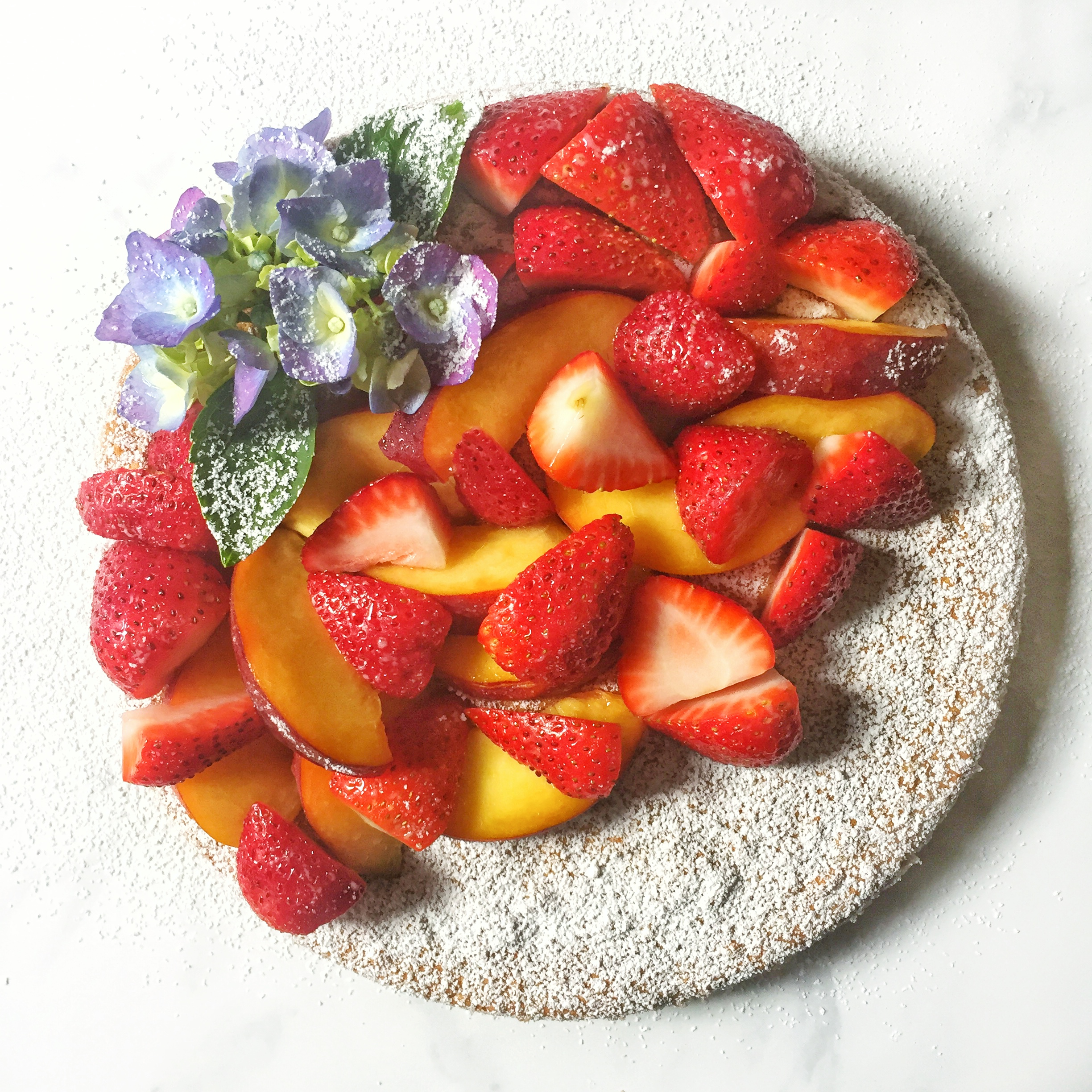 summer almond cake with fresh strawberries and peaches