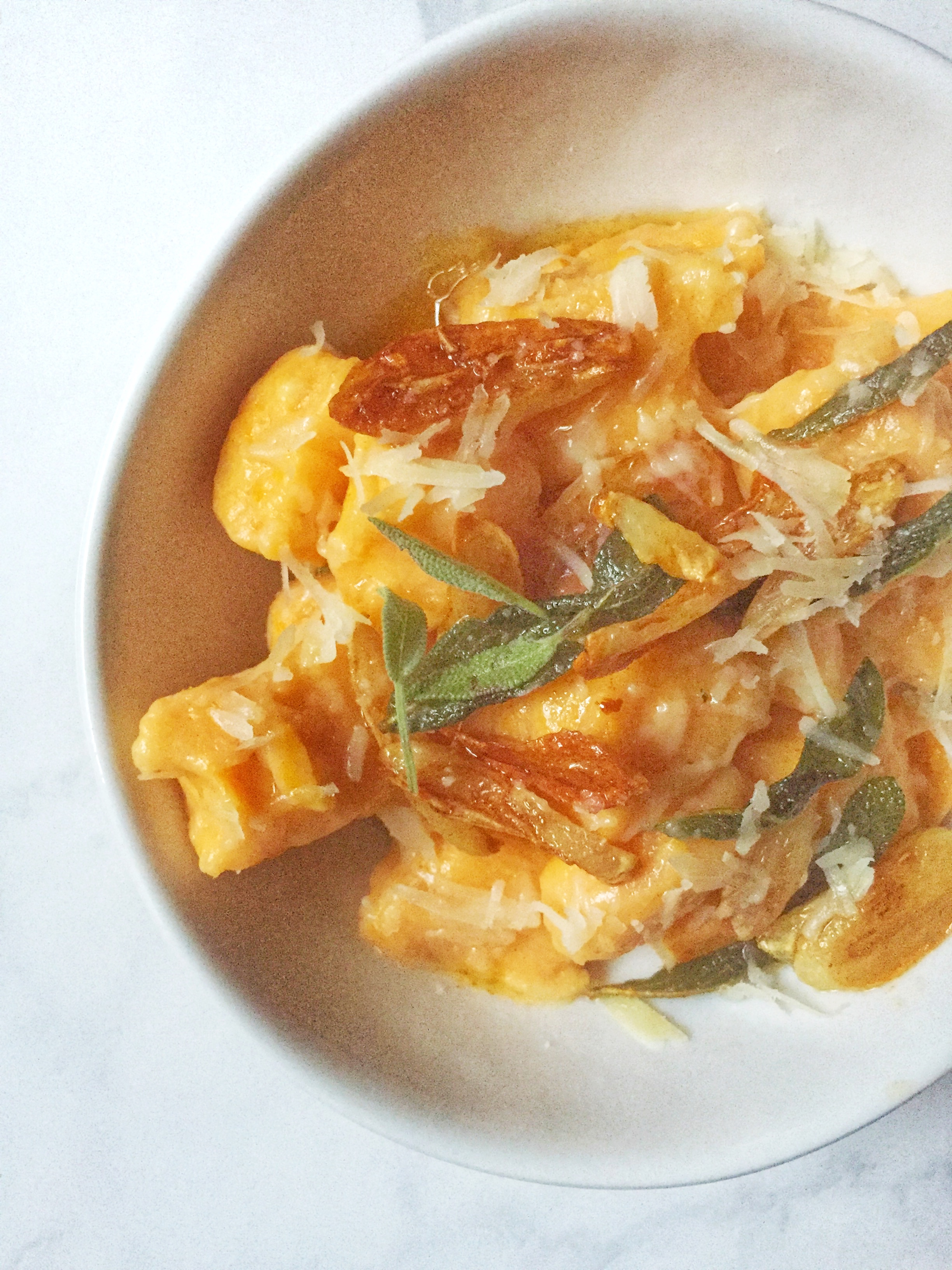 sweet potato & ricotta gnocchi with garlic & brown butter sauce garnished with parmesan cheese & crispy sage leaves