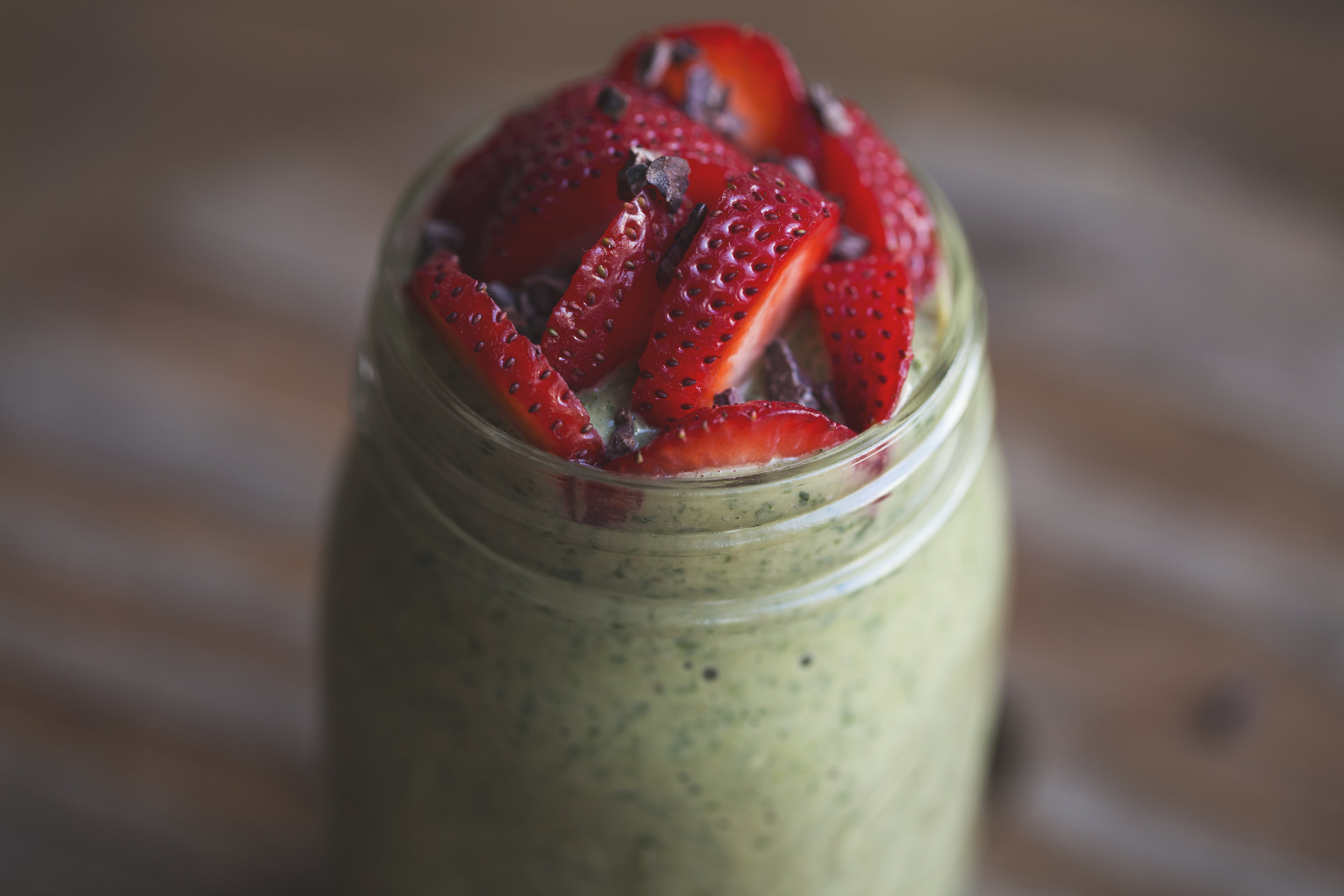 pre-workout green smoothie topped with fresh strawberries and cacao nibs