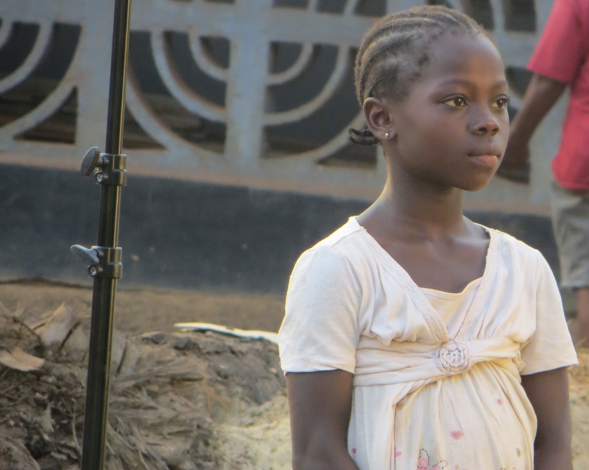 A child watches filming beside a microphone stand in Liberia.