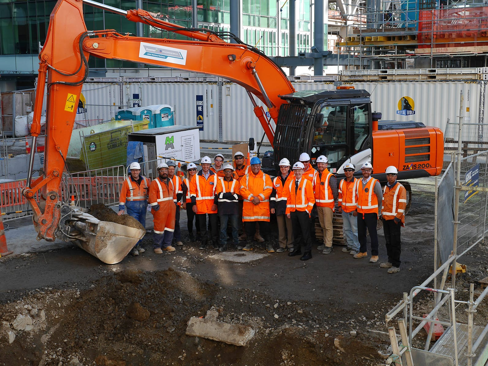 Team from CRL and DSBJV in safety gear beside large excavator, marking the start of the CRL Britomart tunnel excavations