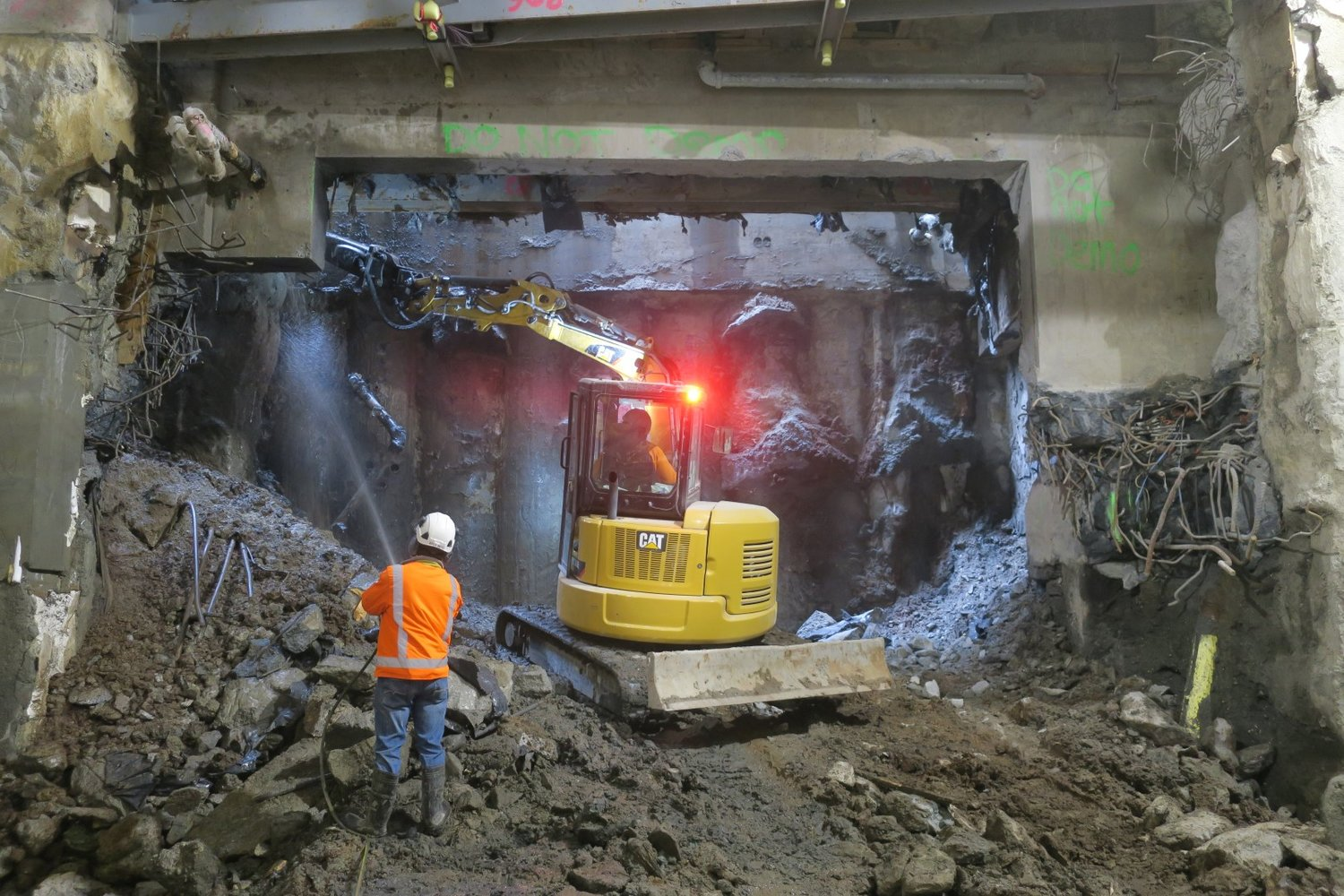 Construction worker and machinery below CPO in the station, cutting through the existing wall between the station and the back of house house