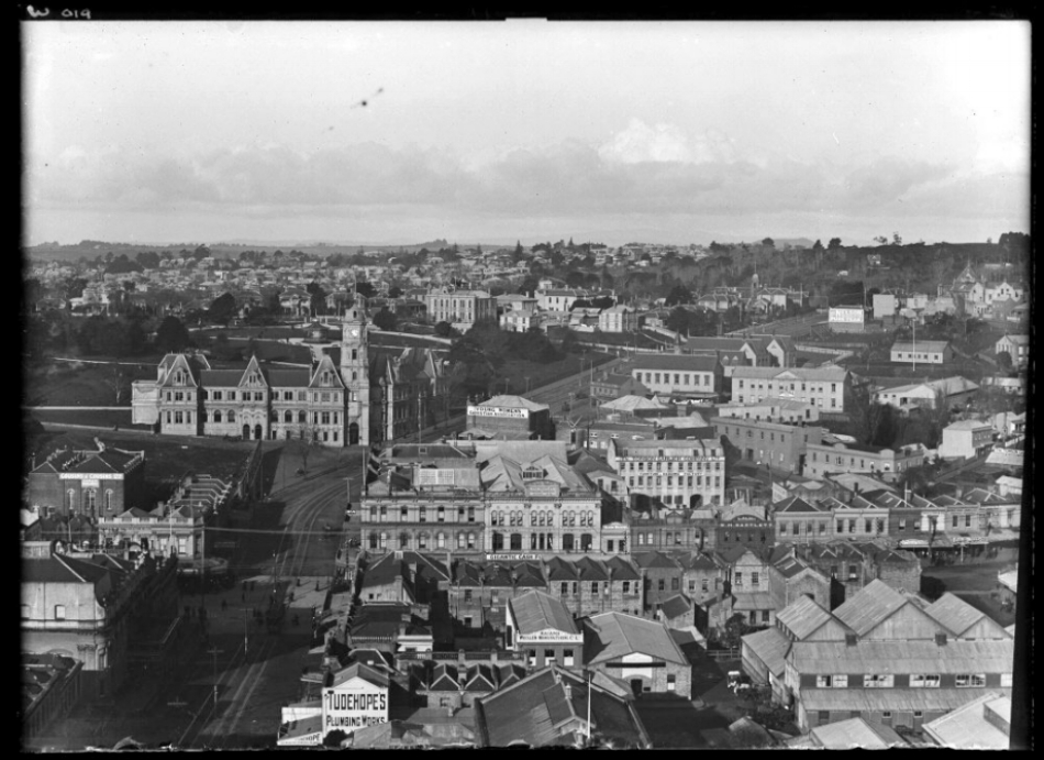 1906: Looking down Wellesley Street West towards Wellesley Street East showing Auckland Public Library with Albert Park behind, Princes Street left off Wellesley Street East with police station on corner of Princes and O'Rorke Streets, Park Hotel (centre right middle distance), YWCA (centre, middle distance), St Pauls Church, top right, Drill Hall, Tonson Garlick Company Limited (right), Abbots Opera House (bottom left) with business on Queen Street from Wellesley to Rutland Streets (Photo: Sir George Grey Special Collections, Auckland Libraries, 1-W19)