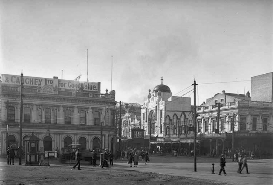 "1927: Note the tramlines and the tram control ""cabin"" (in the centre) at this intersection of Queen and Wellesley Streets. Smith and Caughey's is left) and premises on the east side of Queen Street including Regent Theatre (centre), Somervell's Tea and Luncheon Rooms, Melba Fur Company, Cruickshank, Miller and Company, Howie's Music Shop and George Browne Limited (Photo: Sir George Grey Special Collections, Auckland Libraries, 4-7643)"