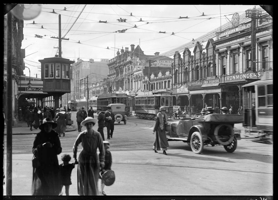 1919: Trams ruled. Looking north east from the southern corner of Wellesley Street West and Queen Street, Auckland Central showing pedestrians, cars and trams in the street, with the premises of Smith and Caughey on the left, and the east side of Queen Street between Wellesley and Victoria Streets, with a tramway control cabin on the corner of Wellesley Street West and Queen Street, the Fountain of Friendship buildings, the Majestic Theatre and Edson's Buildings and the premises White's Belgian Lounge, James Pascoe Jewellers, G W Wright, Pastry Cook and Tea Rooms, J H Dalton City Tailoring Establishment; Samuel Barry (Optician) and Cruickshank and Miller, Ironmongers (Photo Sir George Grey Special Collections, Auckland Libraries, 4-7643)