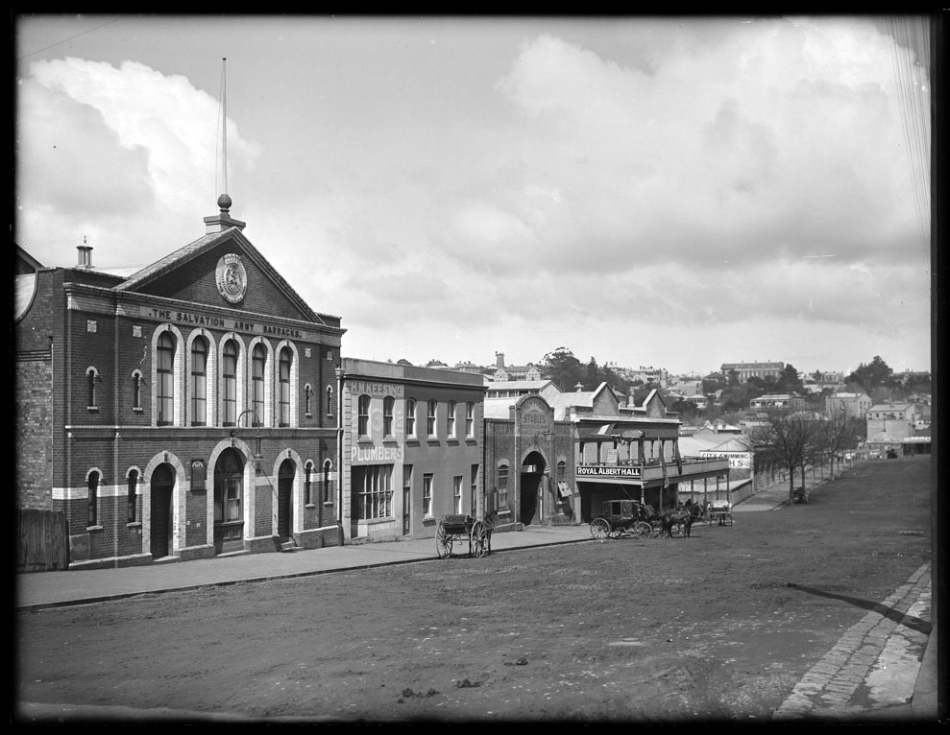 1907: Looking south east along Albert Street from the vicinity of Wellesley Street West, showing premises of the Salvation Army Barracks, H M Keesing, plumber, Pullar Armitage and Company, stables, Royal Albert Hall and the City Fresh Water Baths (Photo: Sir George Grey Special Collections, Auckland Libraries, 1-W887)