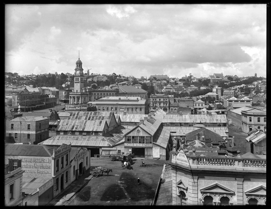 1917: Looking south from Archibald Clark's premises in Wellesley Street West over Market Square towards the Baptist Tabernacle and Karangahape Road, showing the City Markets (centre), Bledisloe Street (foreground), Ethel Buildings (right), premises of D Reid, furniture and produce mart, R Arthur and Company, auctioneers, E Turner and Sons, bulk store, Cook Street (left to right middle distance), O'Leary Brothers and Downs, seed merchants, Market Hotel (centre), Queen Street and Town Hall (left), Greys Avenue, with Myers Park and Kindergarten (distance) (Photo: Sir George Grey Special Collections, Auckland Libraries, 1-W1609)