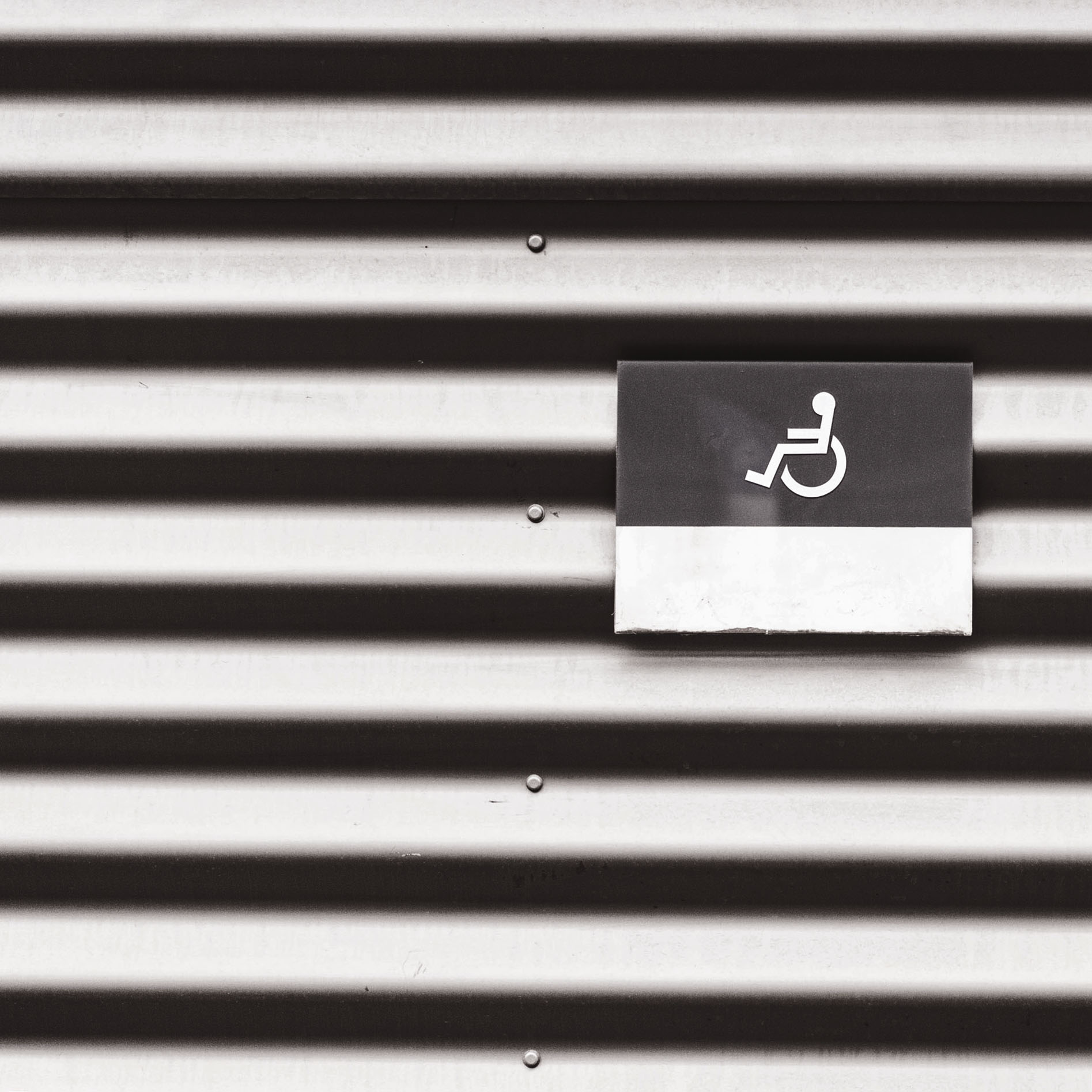 metal-wall-with-wheelchair-disabled-sign-picjumbo-com.jpg