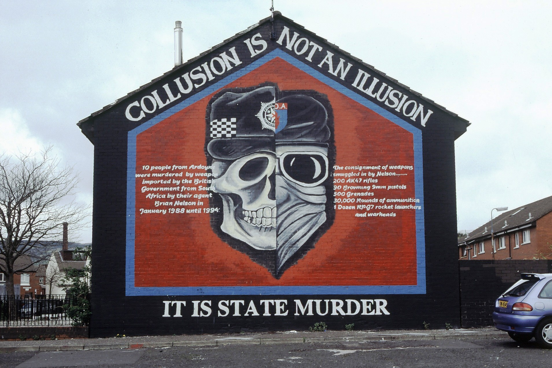 One of the famous gable ends that can still be found in many parts of Northern Ireland. These murals often depict fighters from one of the paramilitary organizations, such as the Republican IRA or a Loyalist group. This particular mural in a traditional Catholic neighborhood reflects the belief among the community that the police acted in league with Protestant paramilitary organizations.