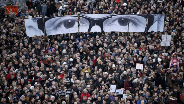 "Hundreds of thousands marched through Paris to commemorate the slain staff of the satirical newspaper. This section of the crowd carries an image of the eyes of the late editor and cartoonist ""Charb""."
