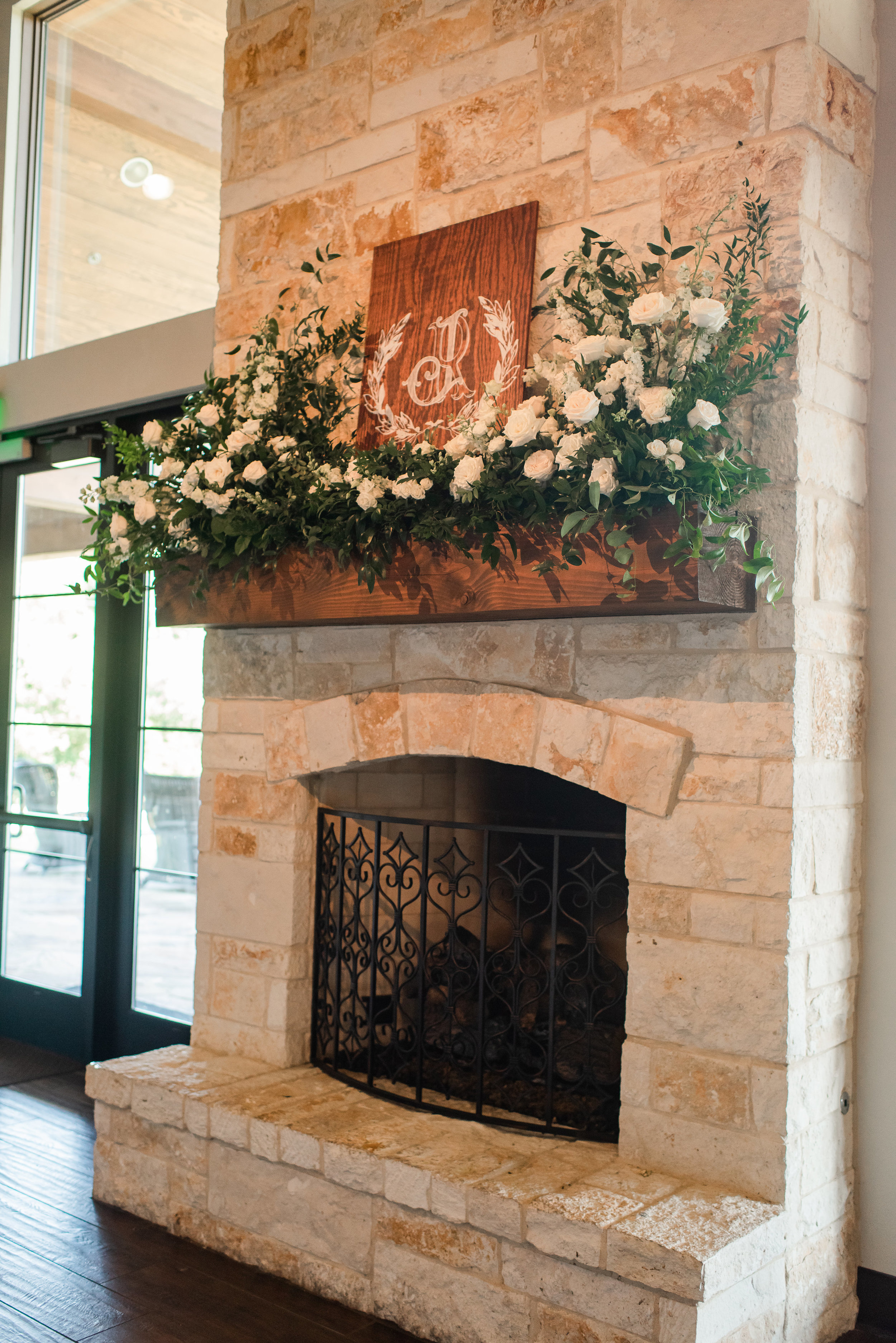 wedding fireplace flowers and monogram sign