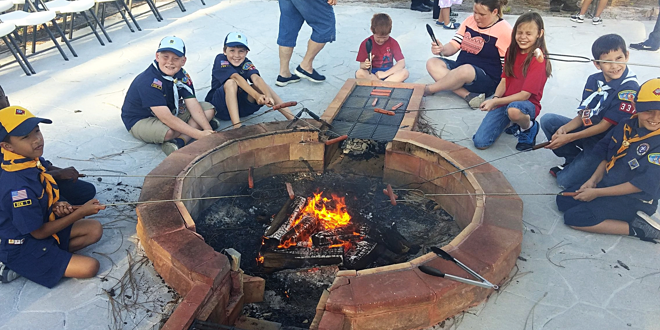 Cub  Scouts & Families from Pack 337 cooking hot dogs on the built-in grill Zachary designed and on skewers!
