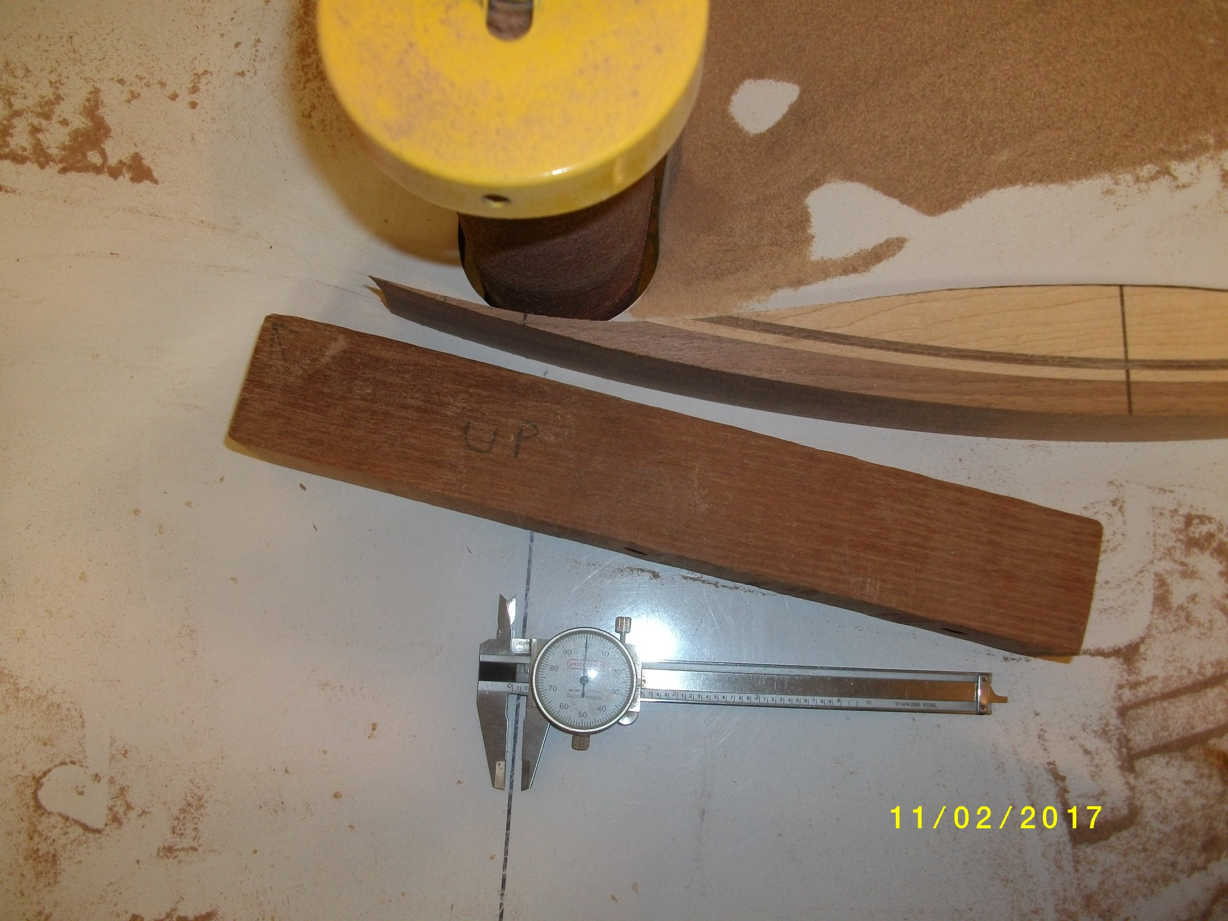Grinding fades, notice the block to back the riser with against the sander. Make sure the sander is square and so is the backer block.