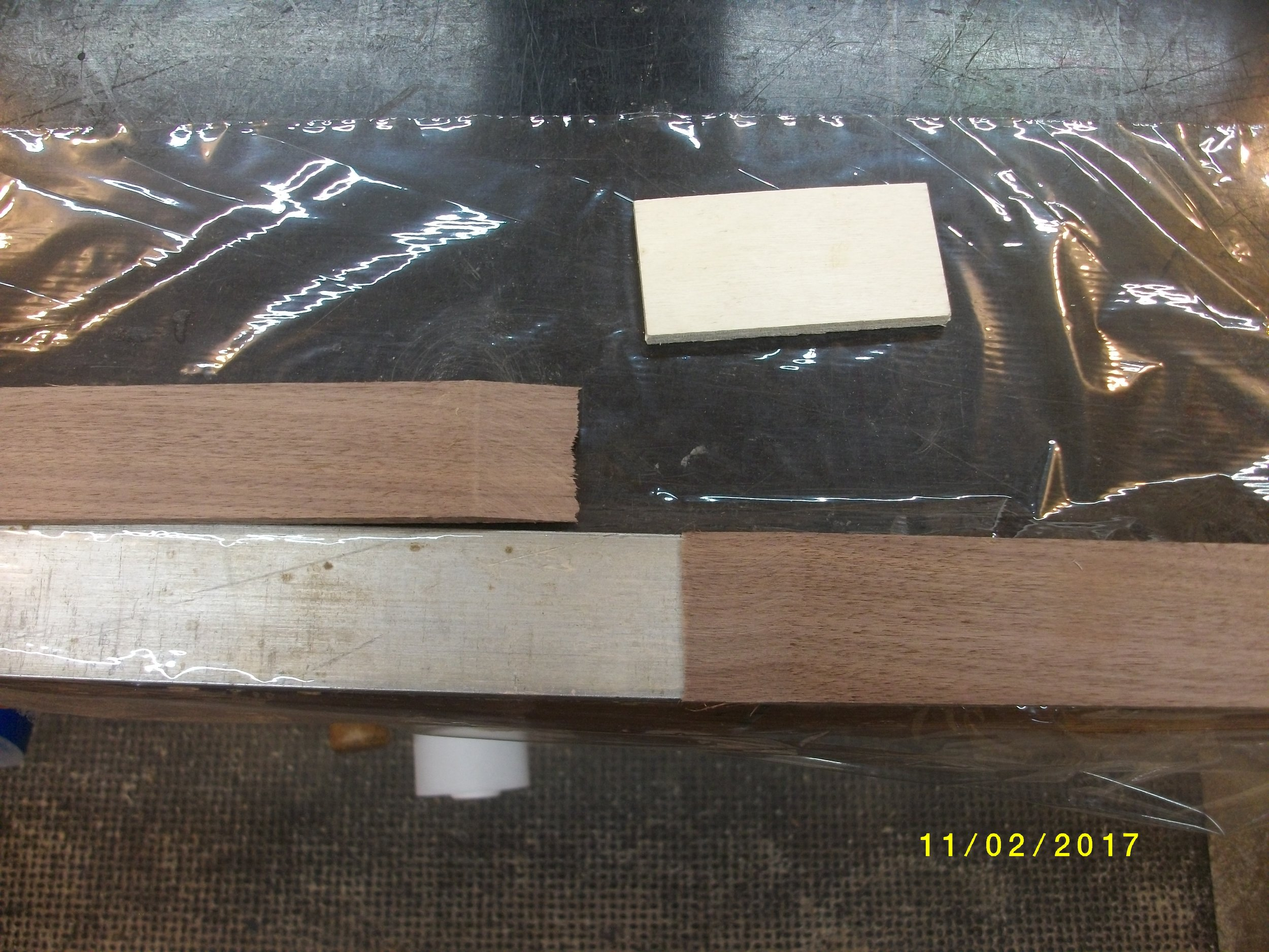 "Now, I have an aluminum bar that is 1.5"" wide, I lay it on the bench edge and lay one lam on it. Clamp that lam at the end away from the glue joint so you only have the other lam and the glue joint to worry about. You need to keep the lam straight when glued so it fits the bow form.  I lay a sheet of plastic wrap under the glue area, and on top of the straightedge.   I apply superglue to both surfaces and then fold the plastic over the joint ,making sure the joint is flush and the second lam is lined up on straightedge, lay a block of plywood on top and clamp the whole thing to bench. Let dry a minute and do the next lam. Take a sanding block to the joint when the glue is completely dry."