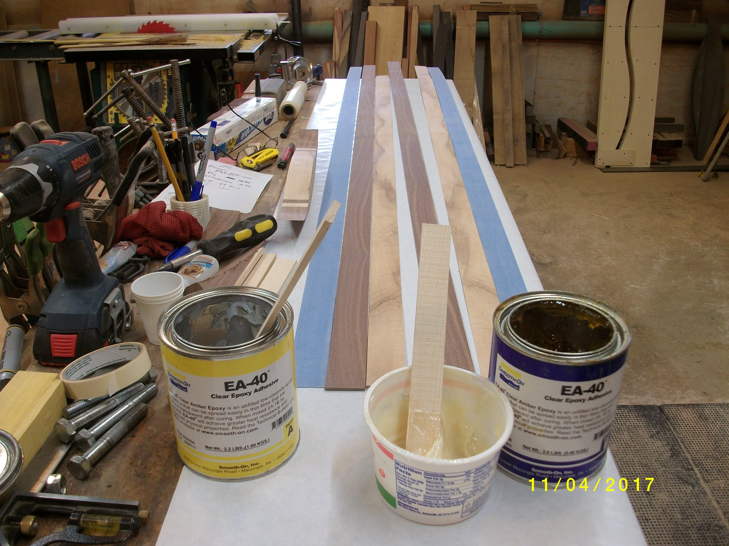 As you can see, I cleaned off part of my bench! Butcher paper taped on where the lams and glass will be, all blown off with clean air. Glue mixed, I went 1/1 with this one, some folks use 2 resin /1 hardener. No pics during actual glueup to save my camera!