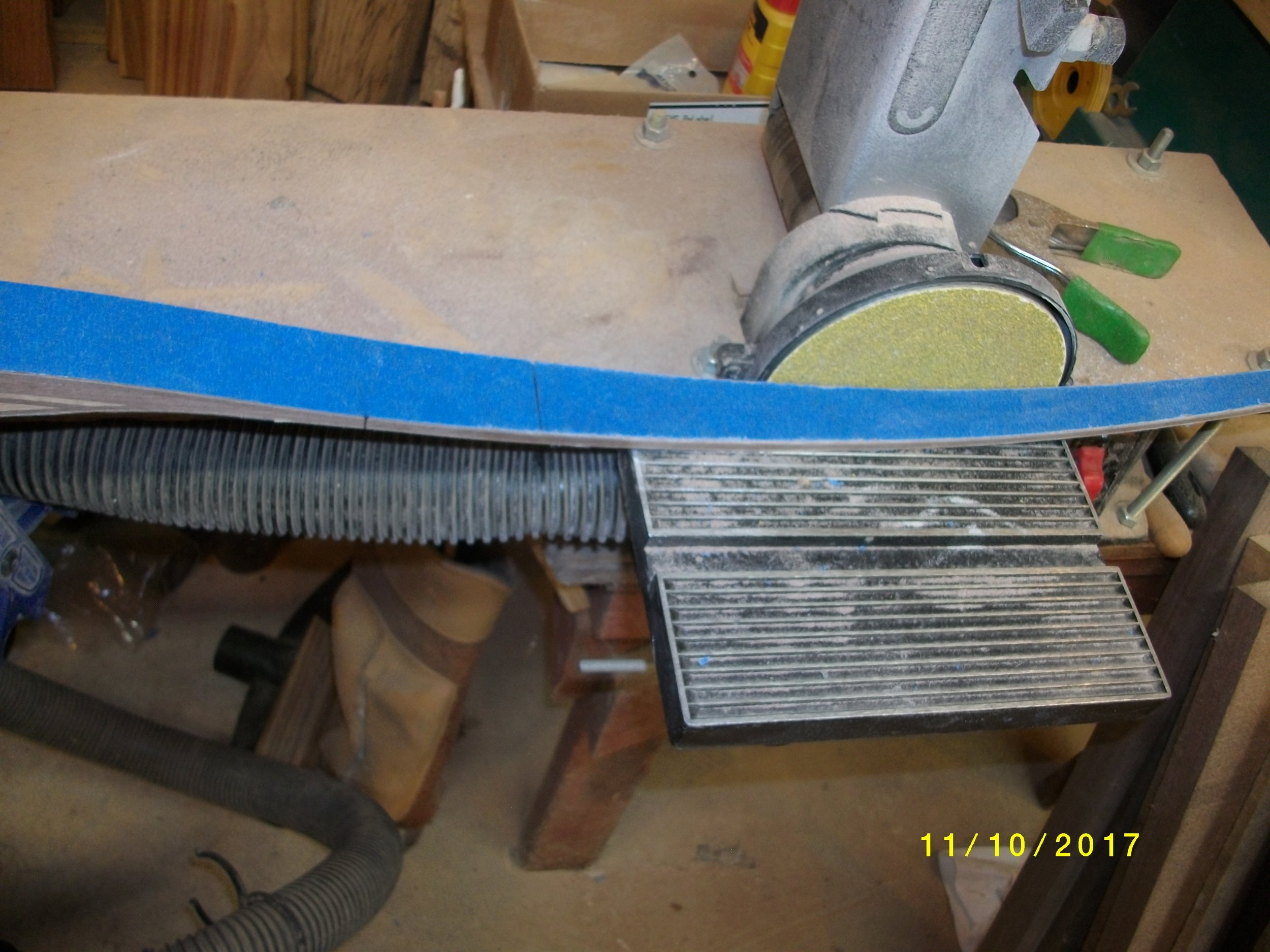 """OK, now I have at the nocks, marked 5/16 each way from the center mark we found with the string. I will end up at 1/2"""" total width but like to start at 5/8"""" in case it needs tweaking a bit.  Then I go out from center 12"""" to get past riser fades, and clamp the yardstick to the limb from the edge of limb at this mark to the mark I measured off center at nocks. Mark ans proceed to cut or grind to the line. I refuse to cut glass with my bandsaw so I grind it on an ancient Skil disc sander with 40 grit paper. Takes about 15 minutes to do a bow, rotating so I don't get anything hot . Slow and easy and don't breathe the dust!! Get some dust collection and a mask for this operation!"""