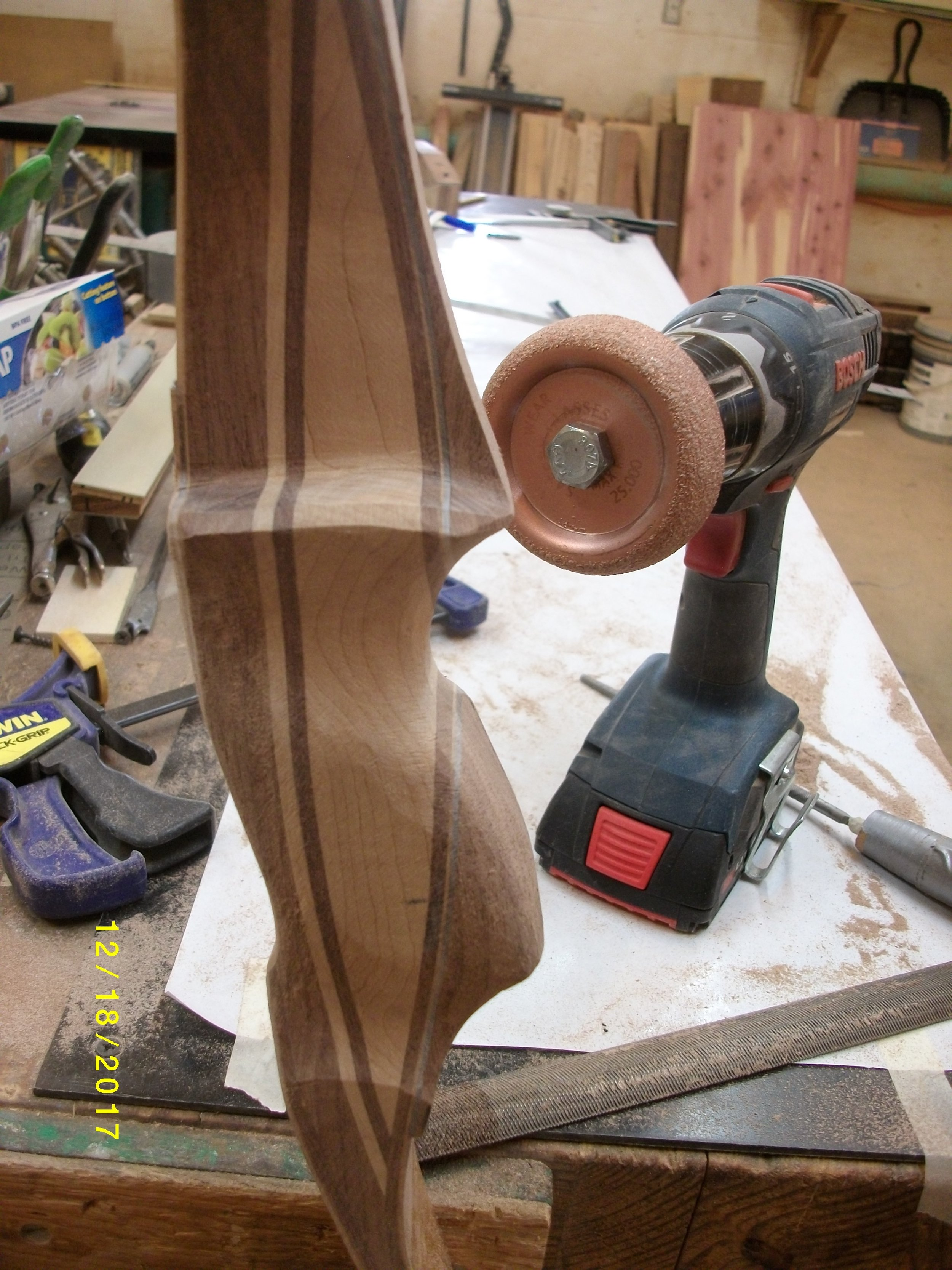 Here I have some more work done on shelf, sight window and grip. Notice the tool in the drill. It is for roughing up rubber to make a tire repair. Works pretty well on shaping, variable speed cordless drill, and when you need to turn wheel the other way so you don't peel the glass loose , just reverse the drill. The glass needs to be worked into the wood always.   Also when you work the limb edges or peel tape, always start at center, or you will pull glass fibers up and ruin a bow!!  Next are just some pics of how the bow is coming along. Will try to finish the bow and build soon!!