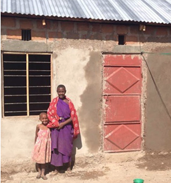 Boma Ng'ombe widow Rose Isaya Palanjo and her daughter Margaret pose in front of their newly built home.