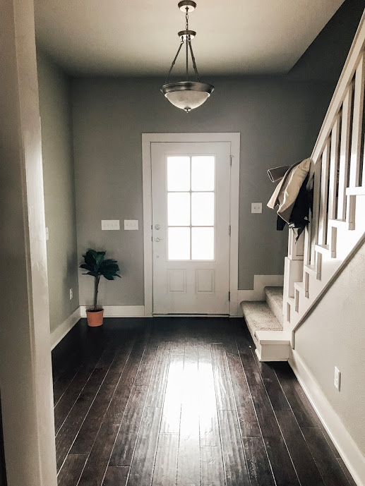 """Our entry is such a great blank slate that invites us to put our own """"stamp"""" on it with minimal effort. I absolutely love the clean lines of the front door and the solid wood railing that leads you to our second floor. I am envisioning a pretty new light fixture, maybe some extra wainscoting and a bench to invite guests to take off their shoes and stay a while."""