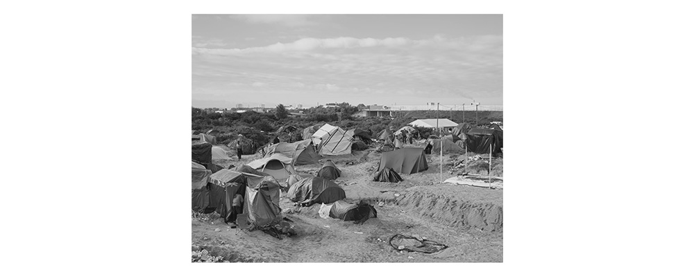 "Image I – The Jungle   The largest illegal refugee camp in Western Europe is just a few hours away from us in Calais. It is a gathering point for refugees who risk their lives to get through the tunnel or by ferry to England. At the time of this photograph, an estimated 3,500 were ""residents"" in the ""Jungle"". Police and fences with razor wire make it virtually impossible to reach a ferry or the Euro Tunnel. Nevertheless, every evening, refugees leave their tents and risk their lives to somehow continue their journey. The camp itself is a legal vacuum. We could only enter it safely in the morning. The closer the time of the evening departure, the more aggressive and unpredictable the mood gets. The frustration of failure then often discharges at night, culminating in violent riots like in May 2016, with many injured. Despite several attempts to evacuate the camp, about 4,000–5,000 refugees still live in the dunes of Calais today."