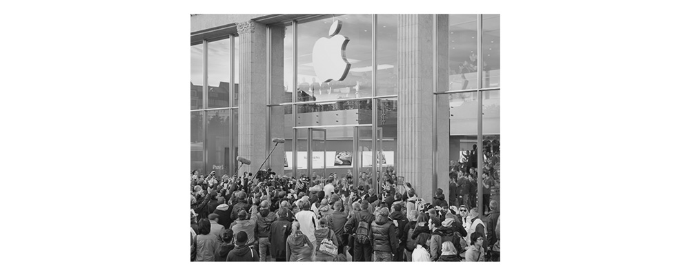 Image IV – Apple Store   During the worldwide sales launch of a new smartphone, thousands of people queue up in front of the apple stores to become one of the first owners of the newest status symbol. Some camp up to two days and nights in any weather in front of the shops, just to be absolutely sure to be one of the earliest to get it. It is not uncommon to see people who get paid to be in line in order to give their place to their client moments before the doors open. When the moment arrives, the so called Apple Geniuses applaud the customers that are pouring in. The press coverage maximizes the notion of an important event. In 2012, within the first 24 hours after the launch of the 680€ priced device, more than 2 million had been sold via the internet alone.