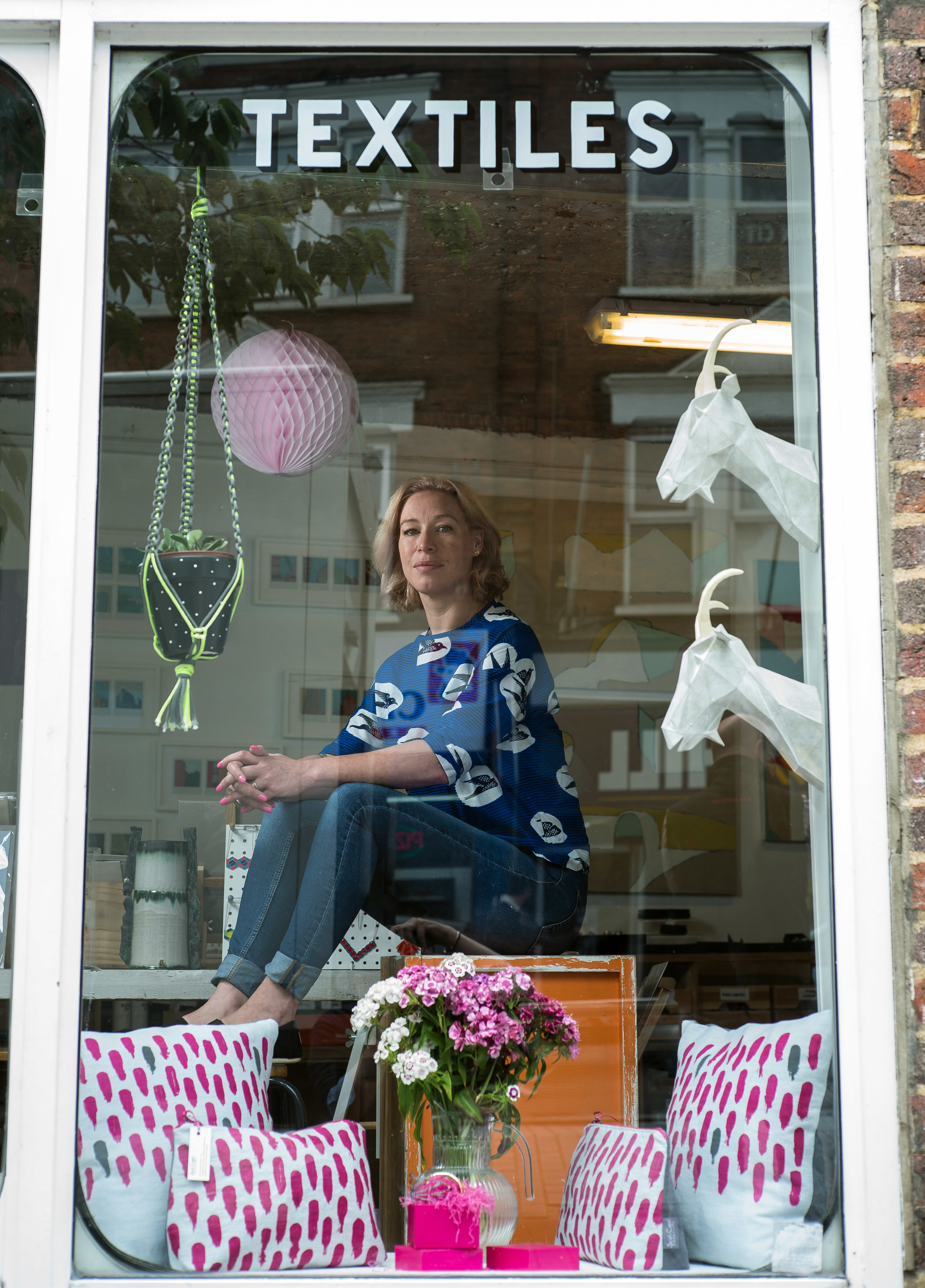 Laura sitting in the window of her shop