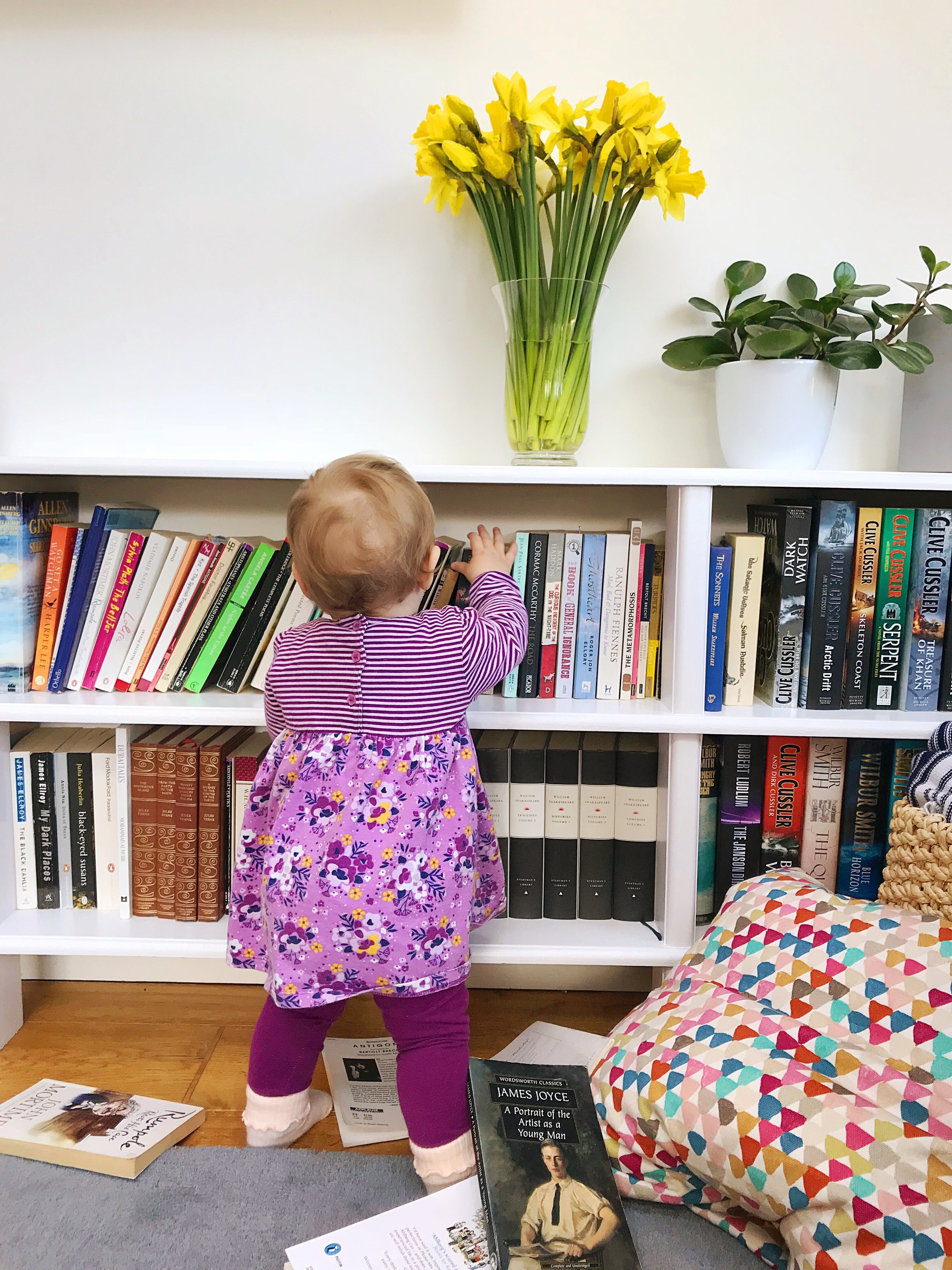 Little person and spring daffs (she merrily emptied most of the books but was happy the entire time).