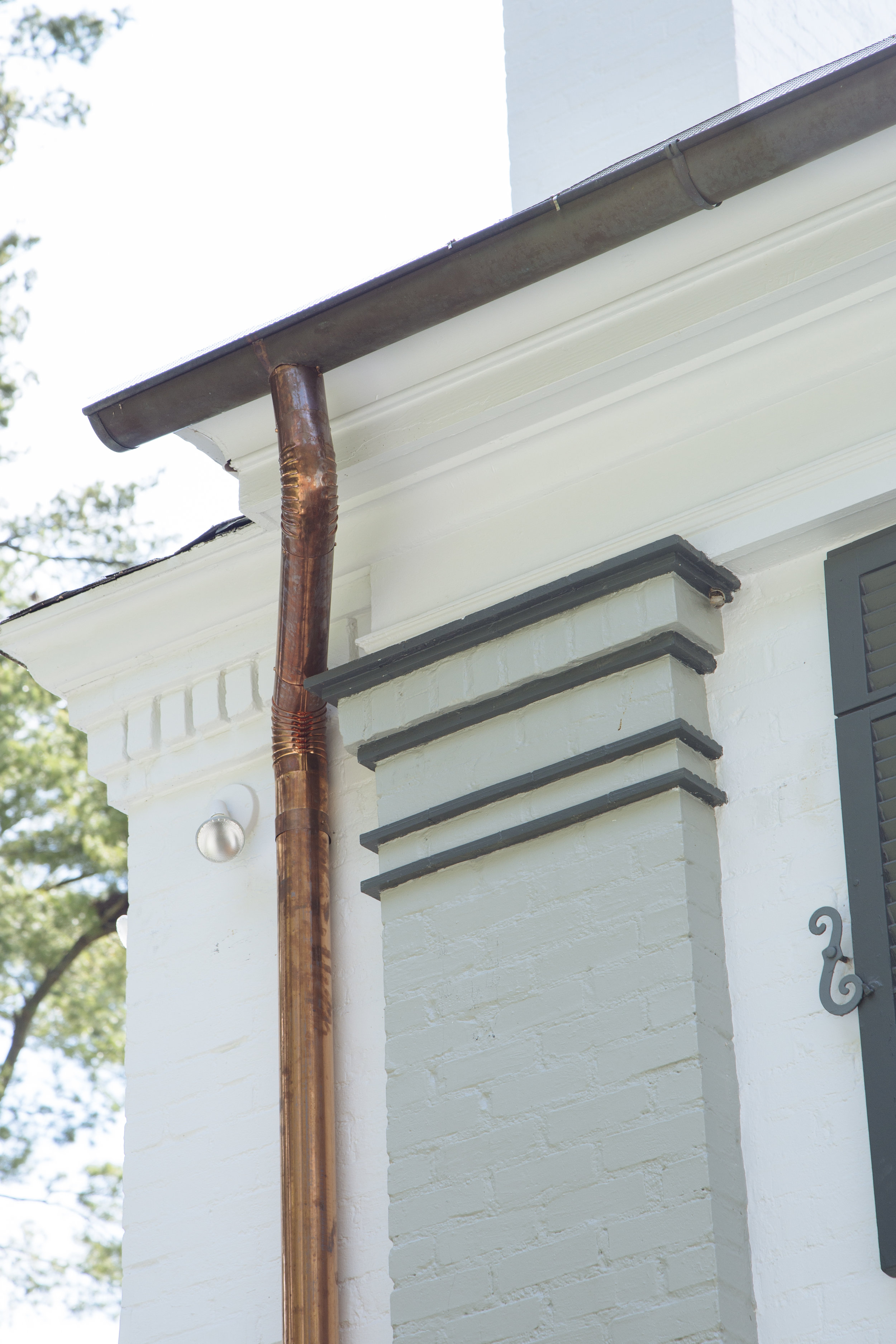 White Brick Home with Copper Gutter Detailing