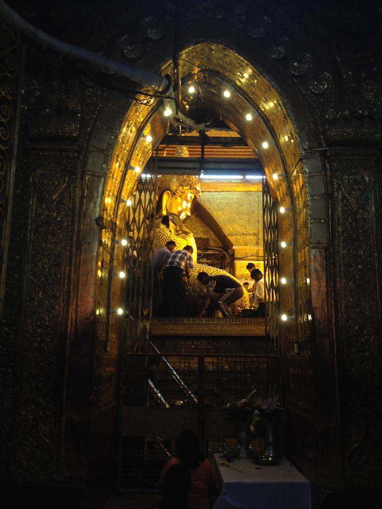Mahamuni devotees applying gold leaves on the buddha