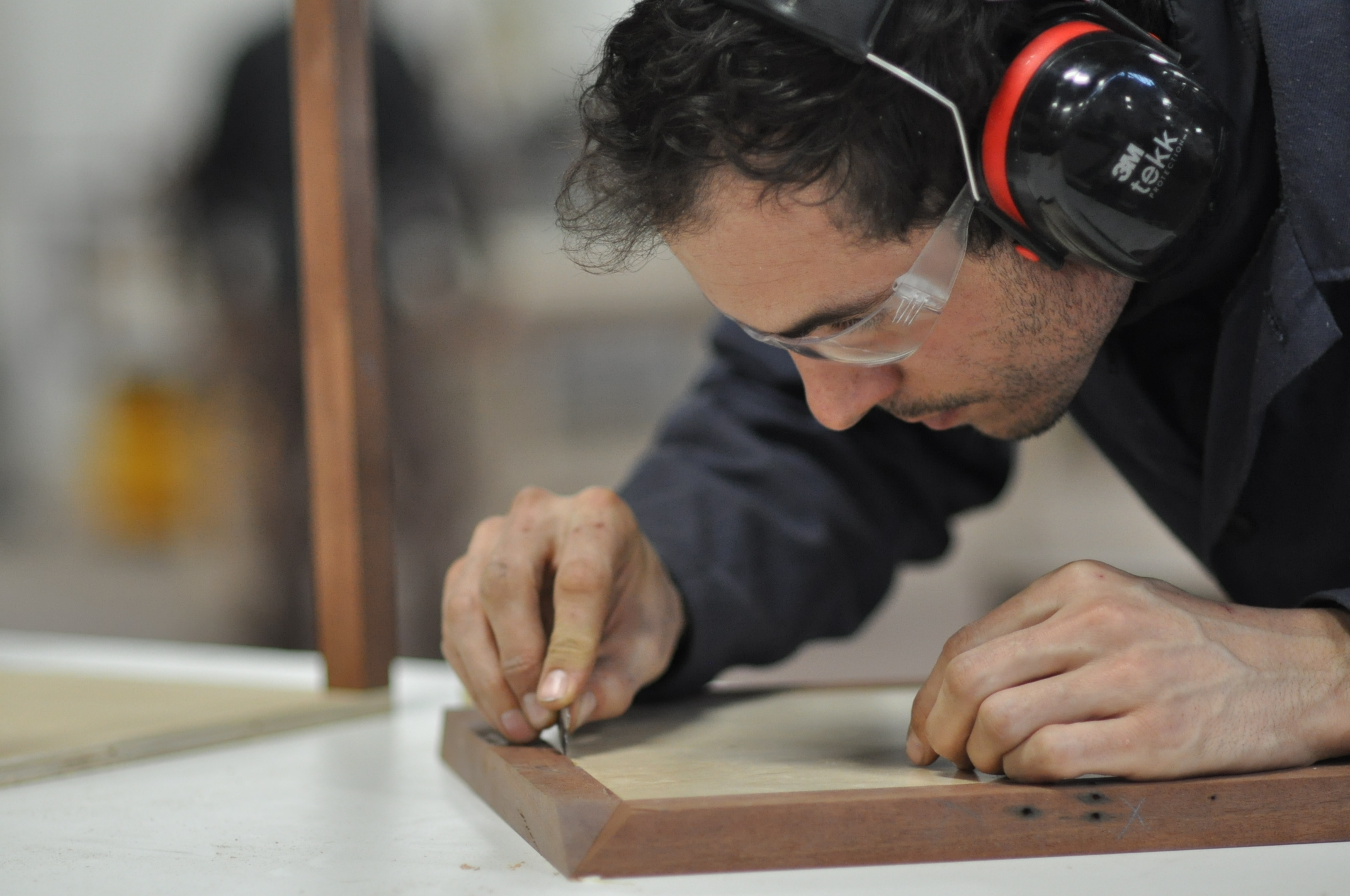 Nathan Dinihanian works on the top of his teak side table.