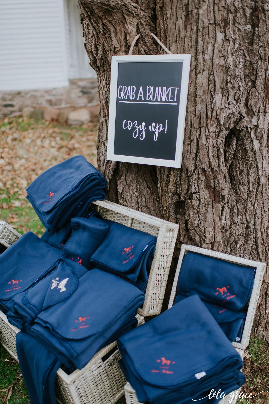 Guests snuggled up in custom monogrammed blankets for their breezy outdoor ceremony.