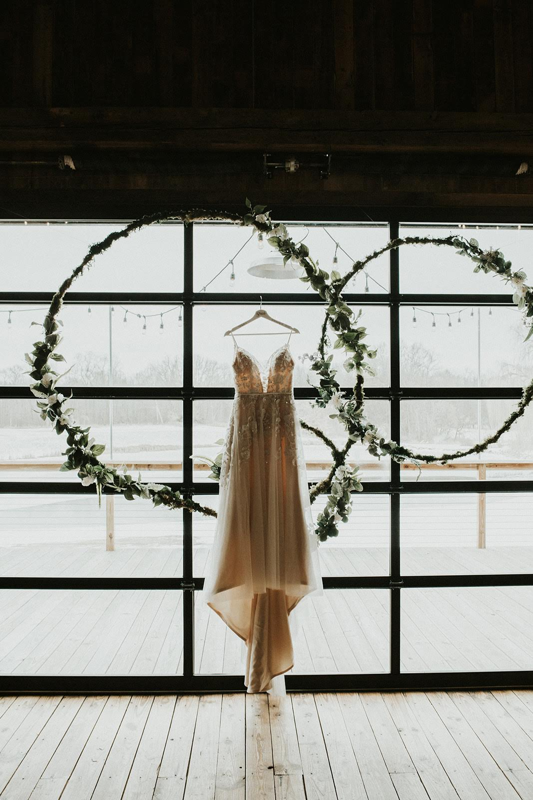 Taylor's gorgeous wedding dress illuminated in the sun, in front of their greenery ceremony backdrop.
