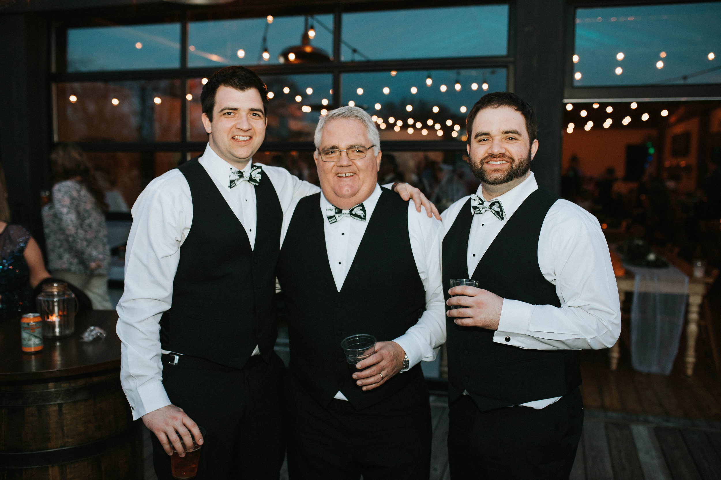 The groom, his dad and brother were surprised with MSU bowties to wear during the game.