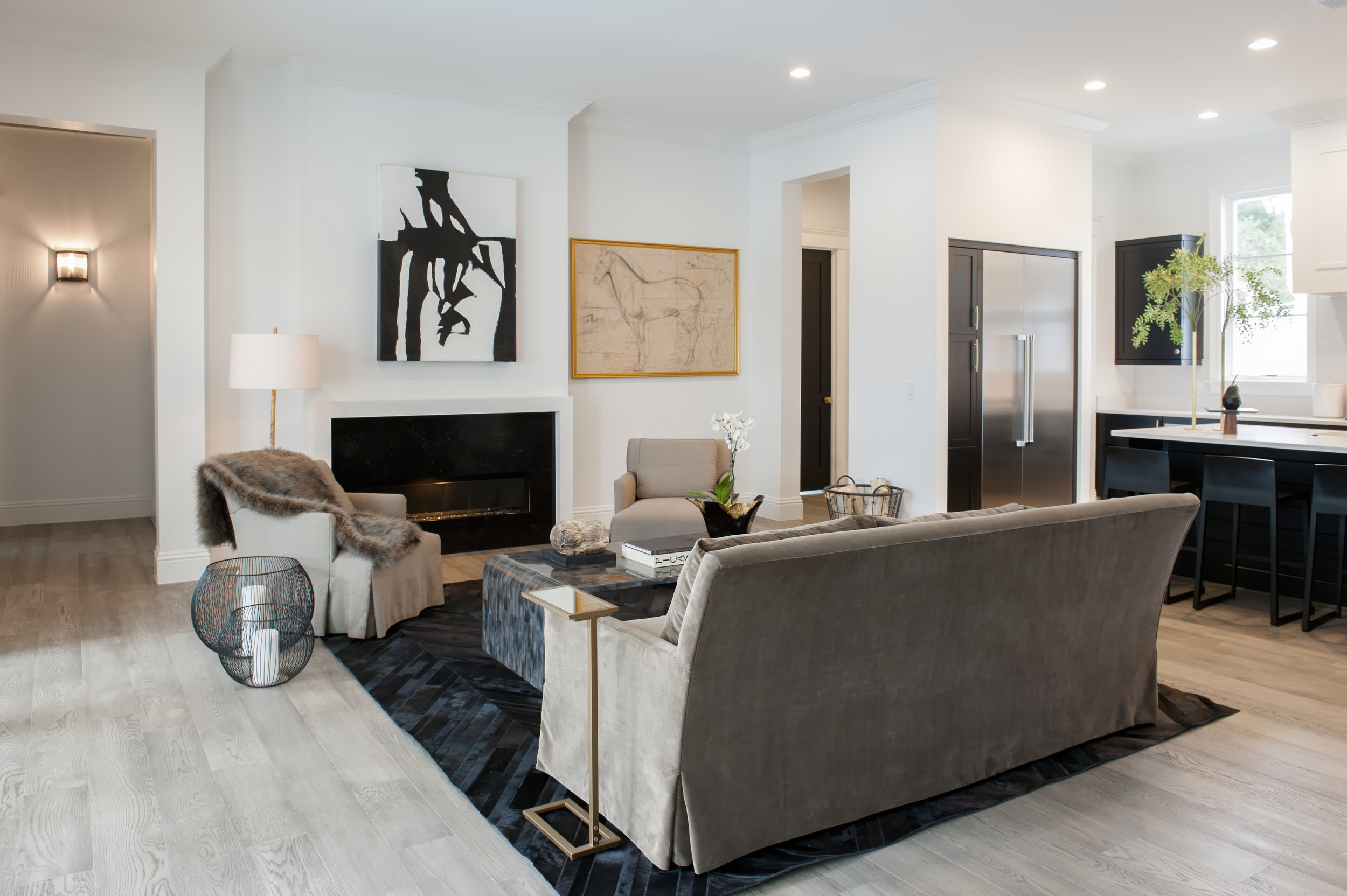 Versatile living room space is essential to showcase the many unique variations to a buyer. A 3-piece seating arrangement creates a communal focal point, allowing conversation to flow in this open concept.