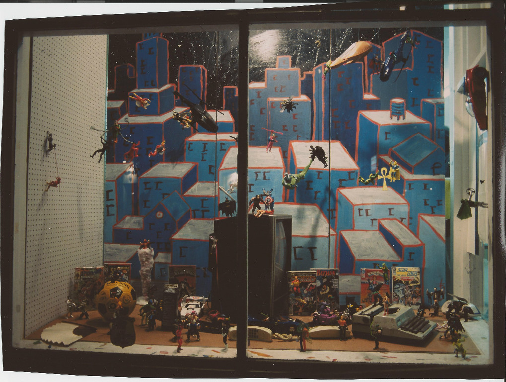 Action Figures. Photo by Dennis McGovern. Window by Brian Hibbs. All characters (c) their respective owners. Window took nearly 8 hours to construct, and within two nights someone broke the glass and stole (only) the Flash figure running up the left hand side.
