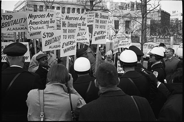 """African American demonstrators outside the White House, with signs """"We demand the right to vote, everywhere"""" and signs protesting police brutality against civil rights demonstrators in Selma, Alabama, 1965 (Library of Congress)"""