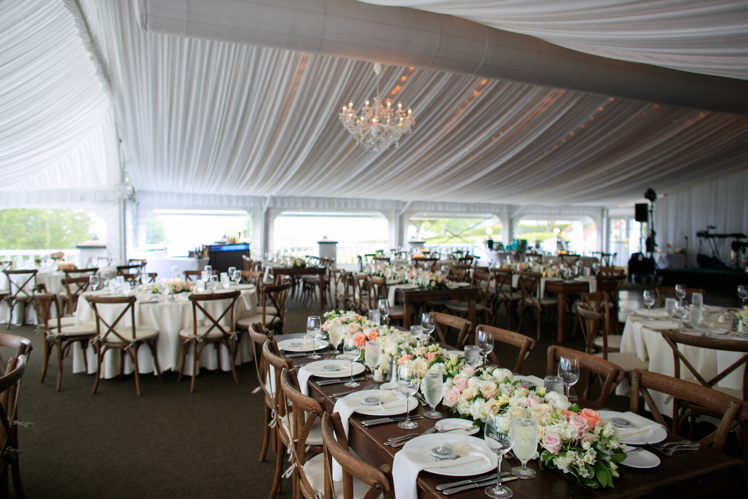 chandeliers, chargers and farm tables used for a tent wedding reception