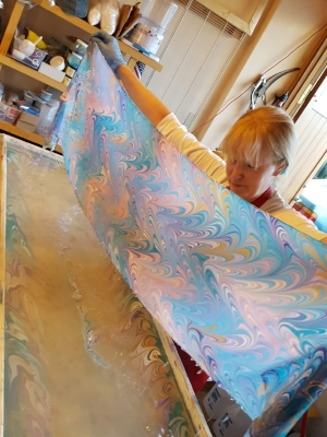 My husband helps me lay the prepared scarf onto the paint: the pattern prints directly onto the silk