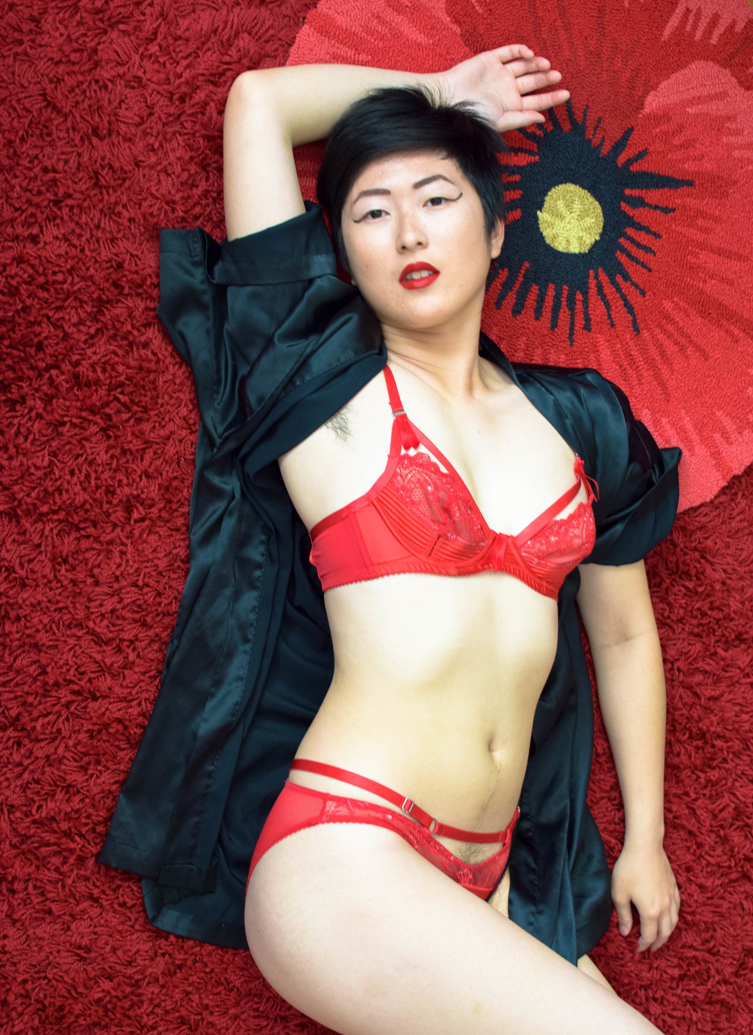 Photo by  Lucy Fleur . Bra and underwear by Dita Von Teese.   Image description: A Chinese-American woman with short hair reclines on a red shag rug and looks directly at the camera. She is wearing a strappy red bra and underwear set and a black robe. Behind her head is another rug in the shape of a large red flower.