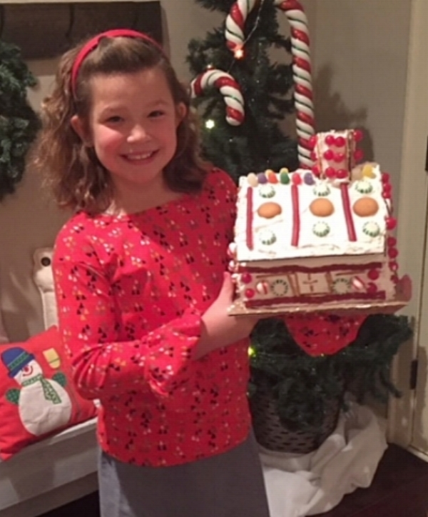 My youngest daugther and her completed gingerbread house.