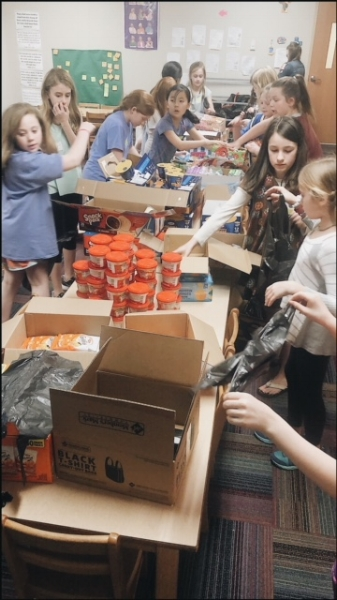 Girls eager to reach the goal of packing 95 food bags!