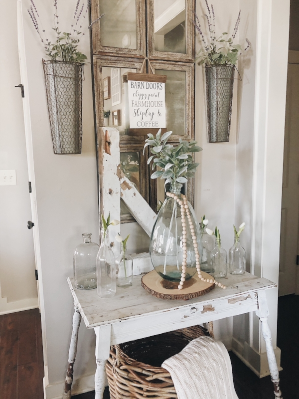Wood bead garland wrapped around an oversized glass jug in our entryway.