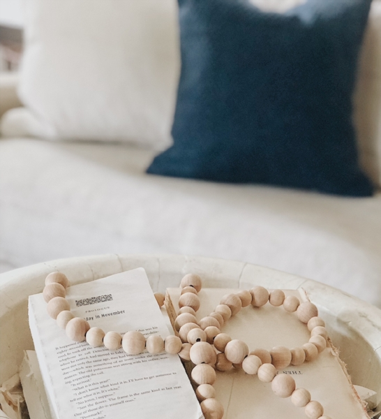 Taking the covers off of unwanted books and placing them in an oversized wooden bowl is an easy centerpiece. Complete the layered look by adding a wooden bead garland. This DIY garland is simple, you can read more about how to make it  here .