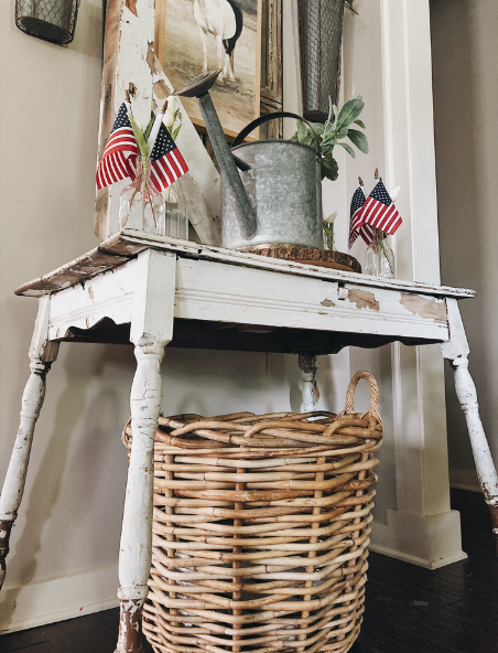 An oversized basket sits underneath a chippy table in our foyer. For further reading on how to create a cozy and inviting entryway, you can head  here.