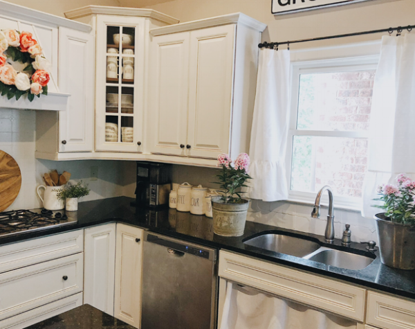 Two custom made linen curtains hang above our kitchen sink and a custom made linen sink curtain below it. To read about how we painted our kitchen cabinets, you can head  here  for all the details.