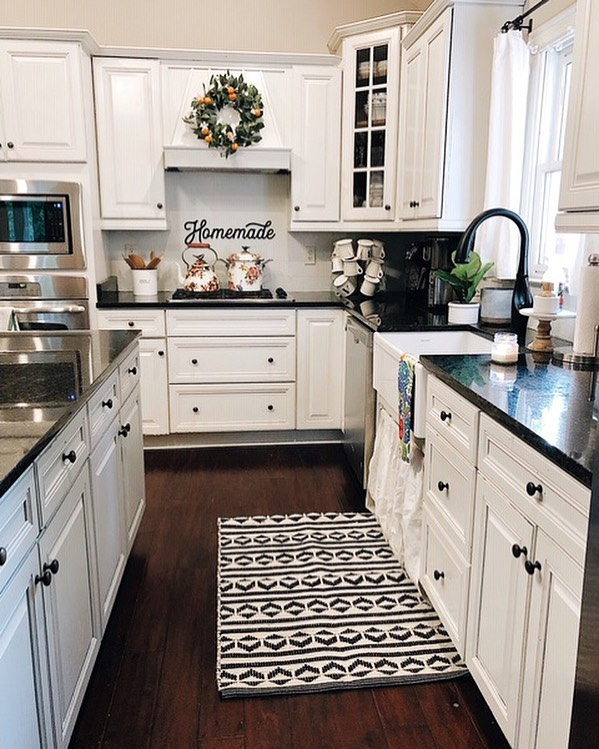 """Happy Sunday friends😆! I'm sharing a view of our summer kitchen tonight as it's going to be changing soon for fall. Some questions that you all have asked about our kitchen, though that stay regardless of seasons,  I thought I'd answer below🙌🏻👇🏻! 👉🏻The """"homemade"""" sign is hanging up by using command strips! @thesimplyinspiredshop who made the sign were the masterminds behind that great idea! This method doesn't peel off painted tile or make holes in it either!👏🏻👏🏻 👉🏻The wreath I change out each season and I simply lean it against our hood. Many had wondered how it stays, but there is a ledge that makes it easy to just lean😍. 👉🏻We painted our cabinets last spring from dark brown to white. I have a 2 part blog series that is on the blog and gives you step by step instructions on everything we did, including paint colors, supplies lists, etc! Tap link in profile to head over to my blog and get started on this DIY👏🏻👏🏻! 👉🏻And last but not least, the black and white rug is linked in my stories 🖤  Im so excited about the week ahead🙌🏻😆; lots of fun things coming on the blog this week and on here ...so stay tuned! If you are interested in learning more about all things faith, family and farmhouse decor topics, I'd love for you to join my weekly newsletter! It's something I love sending out each week and connecting with you all in that way too! You can also tap link in profile to sign up😆🙌🏻!! So grateful for each and everyone of you tonight!! Praying for a great start to your week. 💗💗 #homemade #homesweethome #targetstyle #kitchen #kitchendesign #kitchendecor #kitchensofinstagram #farmhouse #farmhousestyle #farmhousedecor #farmhousekitchen #bhghome #countrylivingmag #southernliving #flowers #cottage #cottagestyle #homedecor #shabbychic #instahome #homesweethome #fixerupper #paintedcabinets #diy #rusticdecor #rustic #americanfarmhousestyle #cottagesandbungalows #kitchens"""