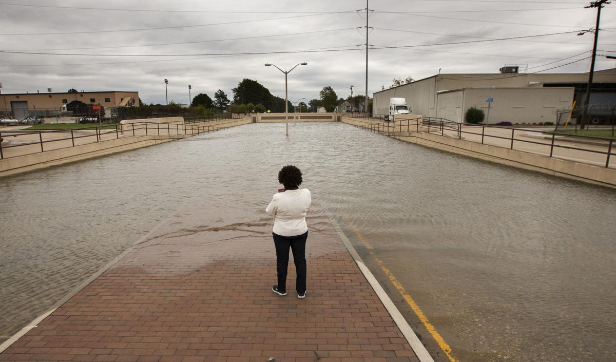 """A passerby stands in the median and looks over the flooded underpass on Virginia Beach Blvd. near Tidewater Drive in Norfolk on Sunday, Oct. 9, 2016."" (Bill Tiernan 