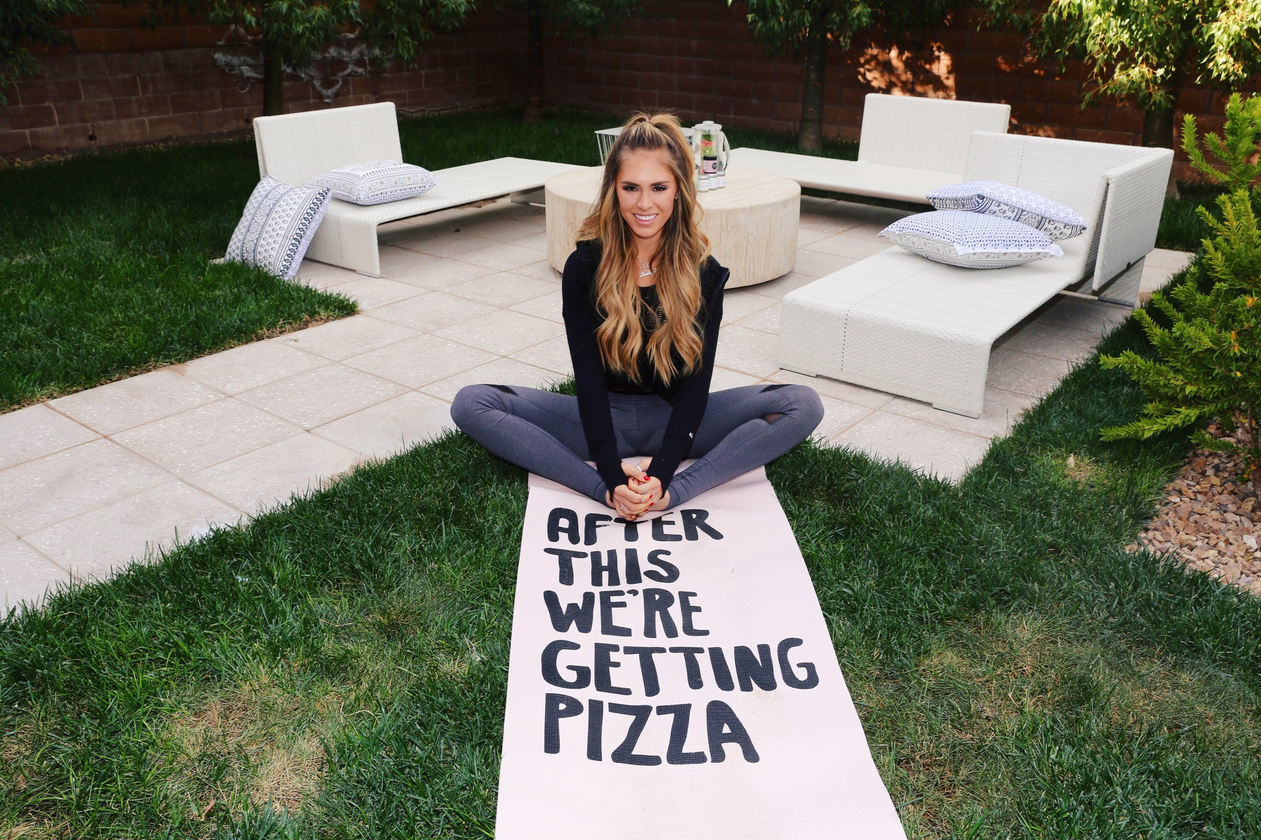 """Kelley Fertitta chilling on her """"After this we're getting pizza"""" yoga mat"""