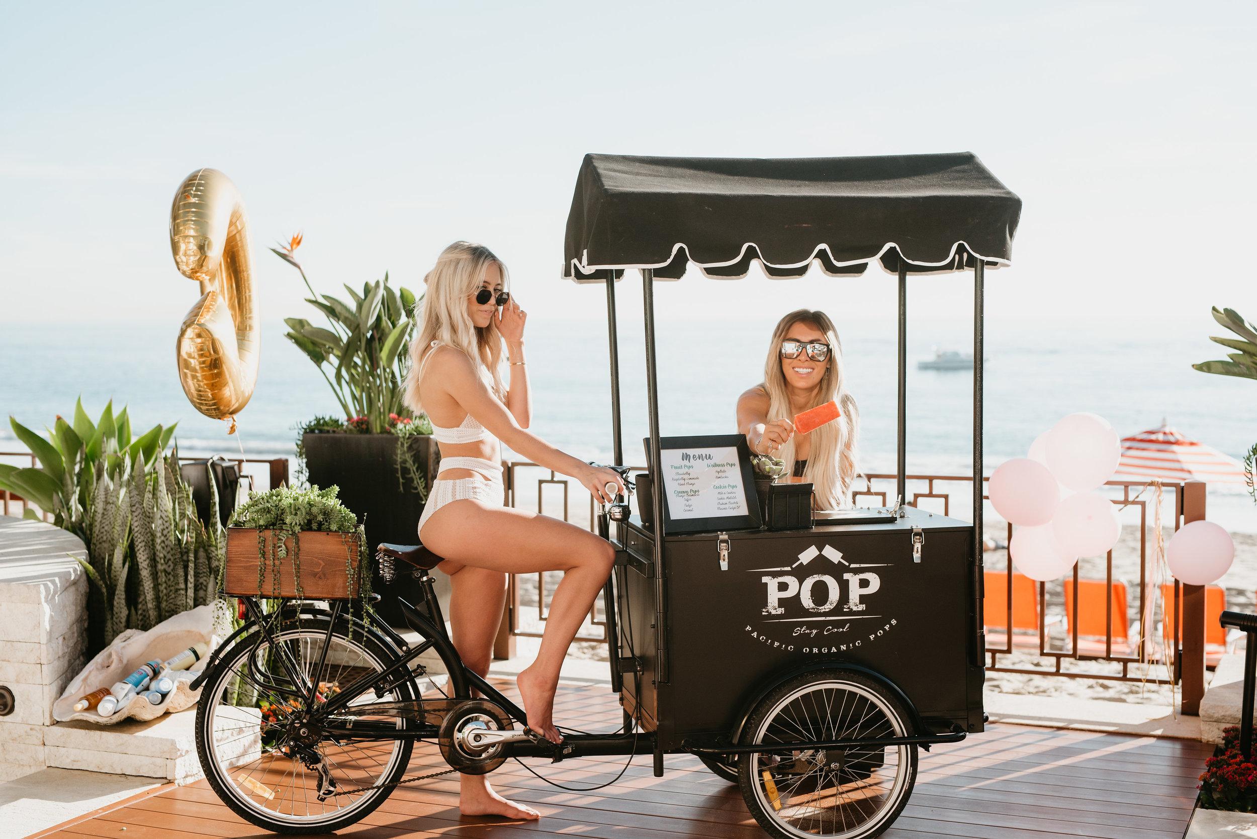 Kelley & Victoria  Fertitta posing with organic pop cart on Laguna Beach